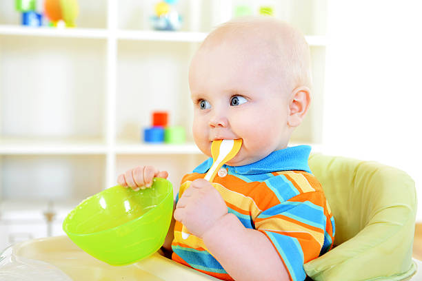 young-toddler-with-plastic-green-spoon-in-his-mouth-picture-id175393954